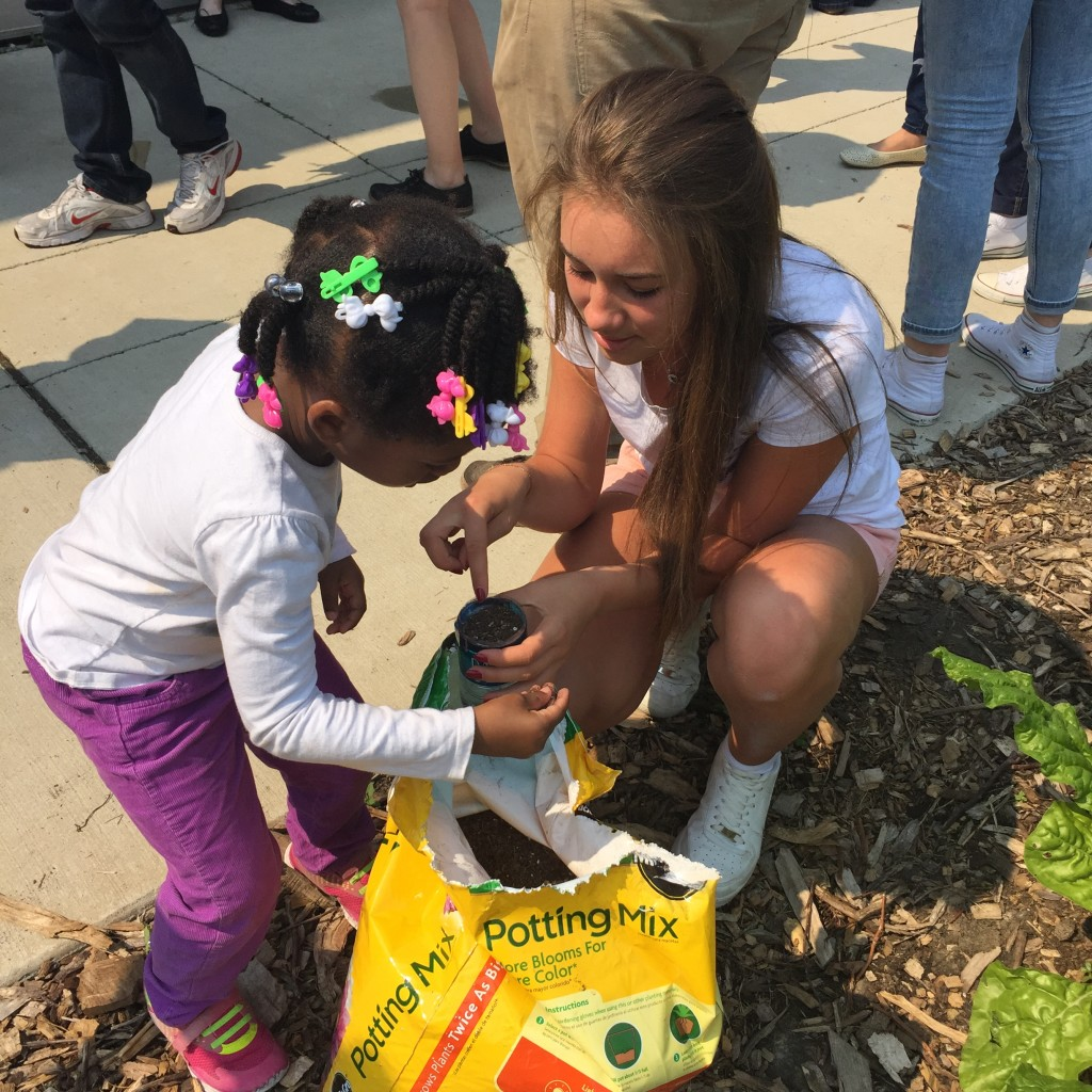 2015 Belarus participate Karyna Vasilyeva building a bottle plant system with a toddler at Educare of Chicago.