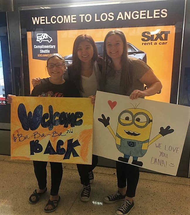 Dana (center) is greeted with a warm welcome by her host sisters at the Los Angeles International Airport.