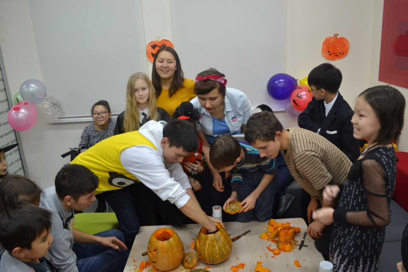 Ruslan helping children carve pumpkins during a Halloween celebration with fellow FLEX alumni.