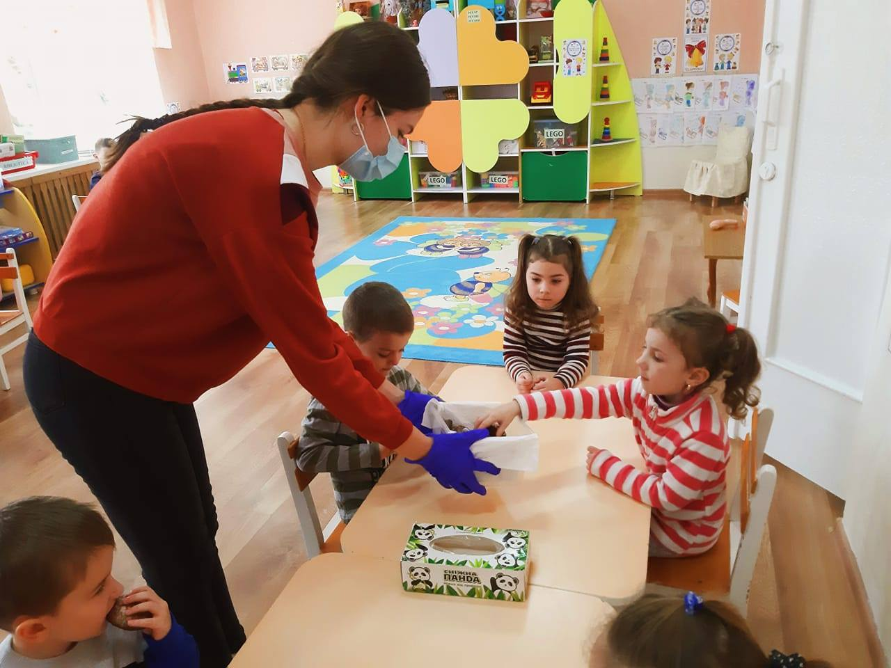 Andreea handing out cookies to her mother's kindergarten class.